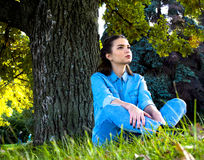 Woman sitting on the grass stock image