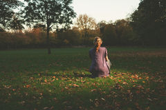 Woman sitting on the grass in evening Stock Photography