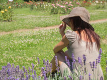 Woman sitting on the grass. Fine woman sitting on the green grass in a hot summer day Stock Images