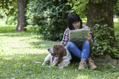 Woman sitting in the grass with her dog, reading the newspaper a stock image