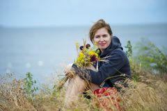 Woman Sitting on Grass Holding Flowers Wearing Black Hoodie Royalty Free Stock Photo