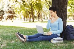 Woman sitting on the grass with laptop outdoors. Concentrated woman sitting on grass focused on working on laptop or preparing for exams in pleasant atmosphere Royalty Free Stock Image