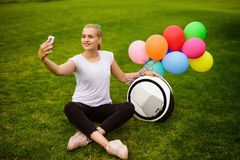 A woman is sitting on the grass. Near the monoclean, to which the inflatable balls are attached. A woman is happy and smiling. She makes selfie on a smartphone stock photography