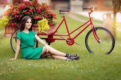 Woman Sitting on Grass Next to a Bike with Flowers Royalty Free Stock Photos