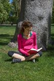 Woman sitting in grass next to tree reading book Royalty Free Stock Images