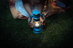 Woman sitting on grass at night and holding hands on lantern Stock Photography