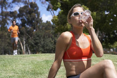 Woman sitting on grass in park, drinking from water bottle, man jogging, focus on foreground Royalty Free Stock Photos