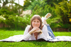 A woman is sitting on the grass in the park Stock Photo