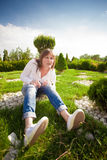 A woman is sitting on the grass in the park Stock Images