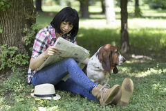 Woman sitting in the grass in the park reading the newspaper and Royalty Free Stock Images