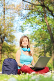 Woman sitting on grass in park and working on laptop Royalty Free Stock Images