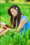 Woman sitting on grass and reading Stock Photos