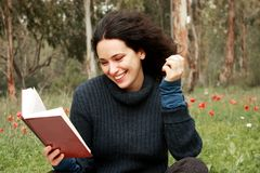 Woman sitting on the grass and reading a book Stock Photography