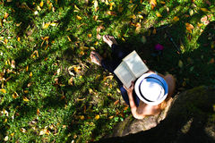 Woman sitting in grass reading a book Stock Photography
