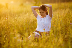 Woman sitting on the grass reading a book Stock Photos