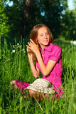 Woman sitting in grass and stroking her hair Stock Image