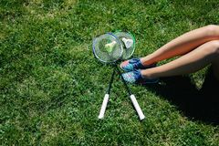 Woman sitting on the grass with two badminton rackets. Woman sitting on the grass with a bottle of water and two badminton rackets at sunset stock images