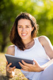 Woman sitting on grass and using digital tablet Royalty Free Stock Images