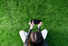 Woman sitting on the grass and using a tablet Royalty Free Stock Photography