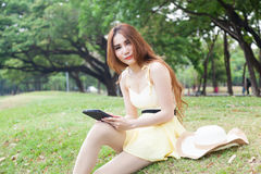 Woman sitting on grass and using a tablet. Royalty Free Stock Images