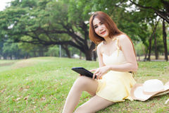 Woman sitting on grass and using a tablet. Stock Images