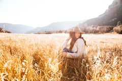 Woman Sitting on Grass Wearing Sun hat Field Stock Image