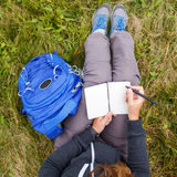 Woman sitting on grass and writing into notebook. Stock Photos