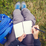 Woman sitting on grass and writing into notebook. Royalty Free Stock Image