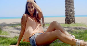 Woman Sitting on Grassy Ground at the Beach stock video