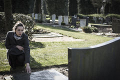 Woman sitting at grave. Woman on graveyard sitting at grave of deceased relative. Sad, mourning Royalty Free Stock Photography