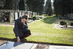 Woman sitting at grave. Woman on graveyard sitting at grave of deceased relative. Sad, mourning Royalty Free Stock Photo