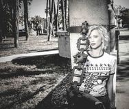 Woman Sitting Beside Gray Concrete Post Grayscale Photo Stock Image