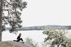 Woman Sitting on Gray Soil Near Body of Water Royalty Free Stock Image