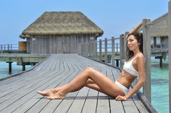 Woman Sitting on Gray Wooden Resort Bridge royalty free stock images