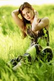 Woman sitting in a green field Stock Photo