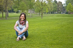 Woman sitting on a green grass Royalty Free Stock Photos
