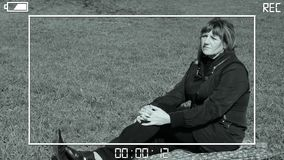 Woman sitting on green grass. Simulation through the viewfinder stock footage