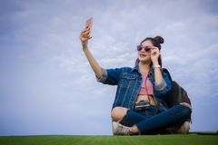 Woman sitting on green grass smiling on the day and photograph s Stock Photos