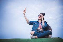 Woman sitting on green grass smiling on the day and photograph s. Elfie smartphone stock image