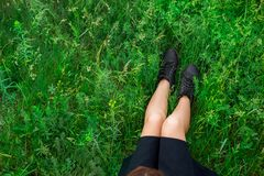 Woman sitting on green grass top view stock photo