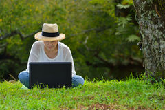 Woman sitting on green grass using laptop computer Stock Photo