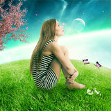 Woman sitting on on a green meadow earth planet looking up at starry sky Stock Images