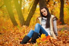 Woman sitting on ground in autmn park Royalty Free Stock Image