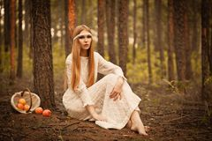 Woman sitting on  ground in the forest Stock Photography
