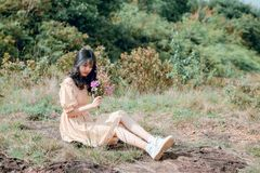 Woman Sitting on Ground and Holding Flower royalty free stock image