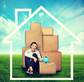 Woman sitting on the ground with many boxes and piggy bank Royalty Free Stock Photography