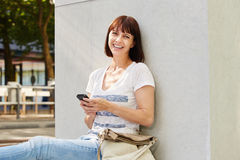 Woman sitting on ground with purse and mobile phone Royalty Free Stock Photos