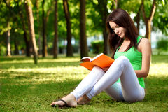 Woman sitting on ground and reading book Stock Photos