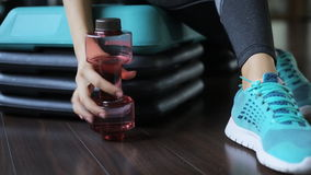 Woman sitting in gym and takes a bottle with sports drink in form of a dumbbell. stock footage