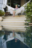 Woman Sitting On Hammock By Swimming Pool Royalty Free Stock Images
